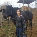 Mosolygós kislány egy barna lóval