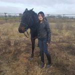 Egy kislány fején kobakkal lovat vezet a kaszálatlan karámban